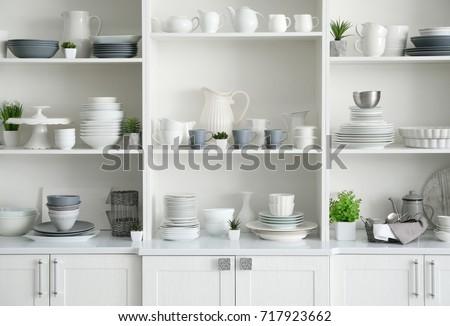 White storage stand with ceramic dishware in kitchen #717923662