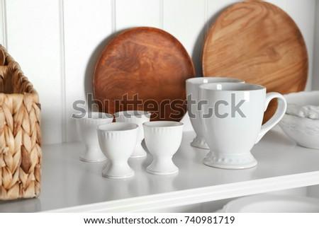 White storage stand with dishware in kitchen #740981719