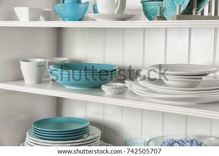 White storage stand with dishware in kitchen #742505707