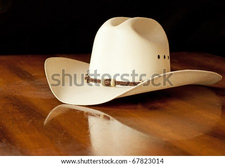 White straw cowboy hat with a hatband on a wooden table against dark background