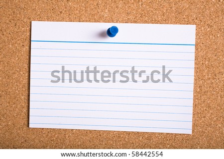 white stripped card with blue pin on cork board