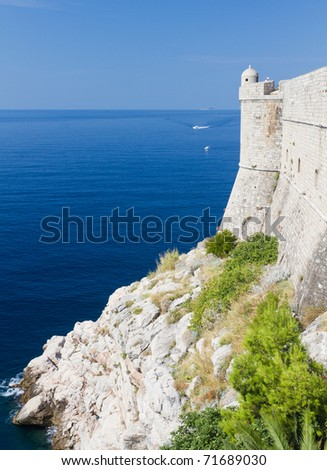 white strong city walls with lookout tower built on rocky shore of Dubrovnik, Croatia