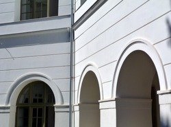 White stucco exterior wall detail with large arches and heavy columns. openings leading to an inner court yard. strong shadows. bright summer light. classical architecture. facade closeup.