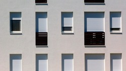white stucco facade detail with windows and french balcony. exterior elevation. abstract flat frontal view. bright summer light. white roll down window shades. modern architecture. home ownership.