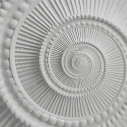 White stucco moulding plasterwork spiral abstract fractal pattern background. Plaster abstract spiral effect background. White gypsum spiral abstract background. Decorative stucco element fractal