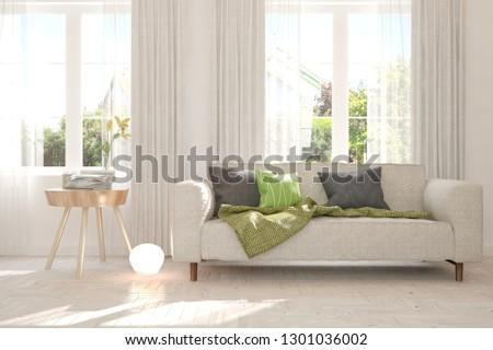 White stylish minimalist room with sofa and summer landscape in window. Scandinavian interior design. 3D illustration #1301036002
