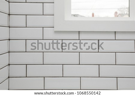 White subway tile wall with a window in it and dark grout for a kitchen or bathroom backsplash