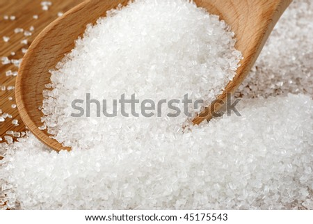 White sugar crystals spilling from wooden spoon.  Macro with extremely shallow dof.