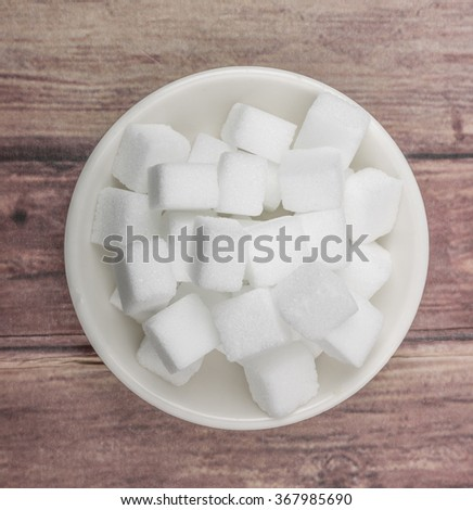 White sugar cube in white bowl over wooden background #367985690