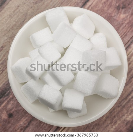 White sugar cube in white bowl over wooden background #367985750