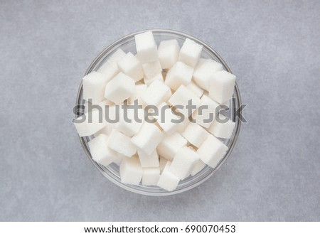 White sugar cubes in center of gray background #690070453