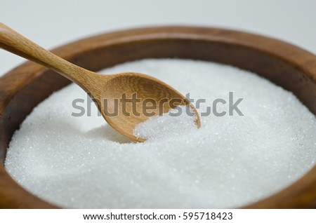 White sugar in a wooden spoon and wooden bowl. Selective focus