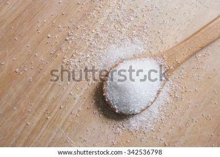 white sugar in wood spoon on wood table