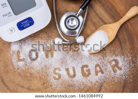 """White sugar in wooden scoop and words"""" low sugar """" letters written in sugar grains, sphygmomanometer, medical stethoscope on wood table background. Healthcare,unhealthy diet and sugar free concept ."""