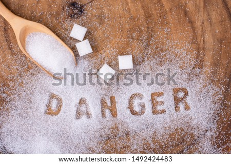 """White sugar in wooden spoon and words """"danger"""" letters written in sugar grains on wood table background. Unhealthy diet ,awareness and stop diabetes concept."""