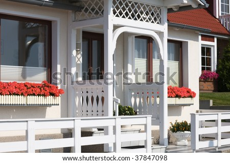 White summer house with geranium