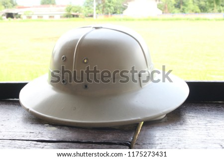 1916c759e8dcb White sun helmet is placed on the balcony with green lawn as background. It  is