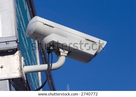 White surveillance camera mounted on the outside of a building