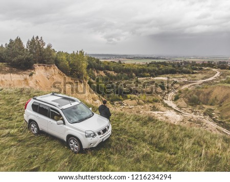 white suv at the top of the hill in autumn overcast weather. man standing near car around wild nature. alone with thoughts