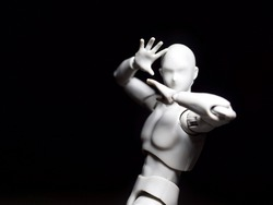 White synthetic humanoid robot action figure doing a bizarre pose against black background