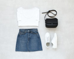 White t-shirt, blue denim mini skirt, small black cross body bag, white sneakers on grey background. Overhead view of woman's casual outfit. Flat lay, top view. Trendy simple basic minimalistic look.