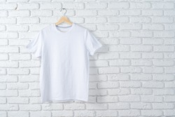 White t-shirt hanging on hanger against brick wall, copy space
