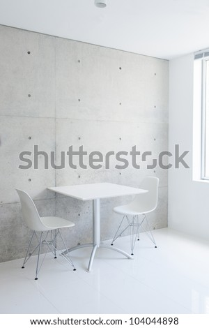 white table and chair against concrete wall