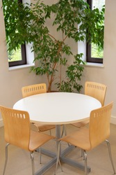 White table and chairs for sitting, kitchen area for staff in the office