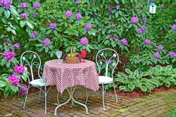 white table and chairs in rhododendron garden with fruit basket on checkered tablecloth