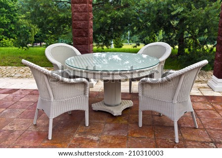 White table and chairs patio furniture in a garden\'s gazibo.