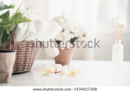 White table, body care products and towel. Bath preparation. White interior of bathroom