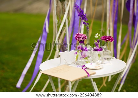 White table for visiting ceremony with the decor and purple flowers on a background of a wedding arch