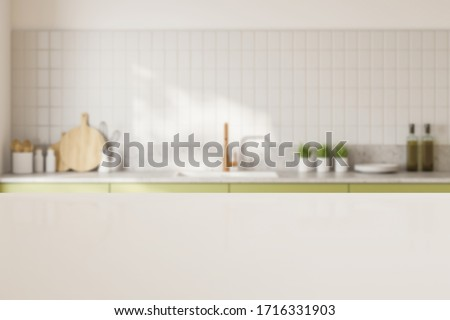 White table for your product standing in blurry kitchen with white tiled walls and green countertops with built in sink. 3d rendering mock up