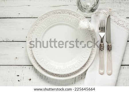 White table setting from above. Elegant empty plate, cutlery, napkin and glass on shabby chic or vintage planked wood table.