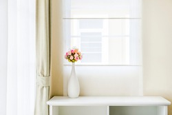 White table with flower vases placed, beautiful bedroom with brown windows and curtains, white translucent curtains.