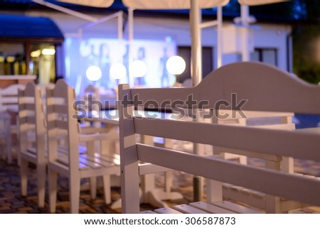 White Tables and Chairs on Outdoor Patio at Night, View of Empty Restaurant or Club Patio from Across Shiny Clean Table Surface