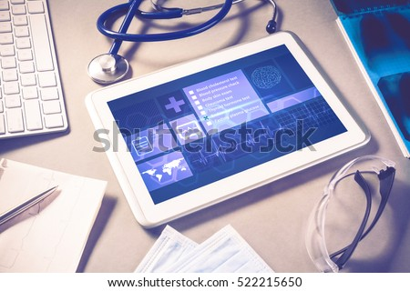 White tablet pc and doctor tools on gray surface #522215650