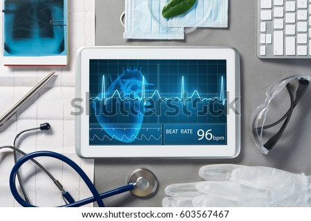 White tablet pc and doctor tools on gray surface #603567467