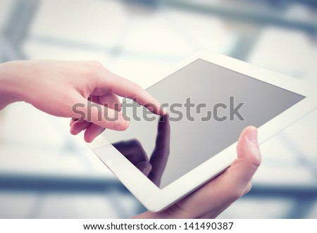 white tablet with a  blank empty screen in the hands