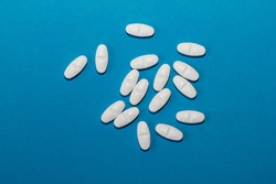 White tablets on a blue background close-up. Macro pills. Medical care for flu and colds. Protection from Covid19