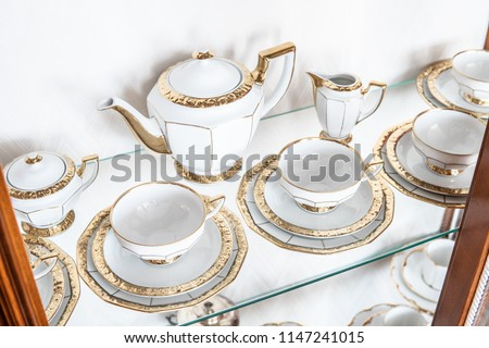 White tableware in cabinet on glass shelf consisting of plates, cups, jug, pot, gold rim as a delicate decoration #1147241015