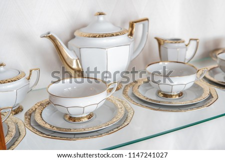 White tableware in cabinet on glass shelf consisting of plates, cups, jug, pot, gold rim as a delicate decoration #1147241027