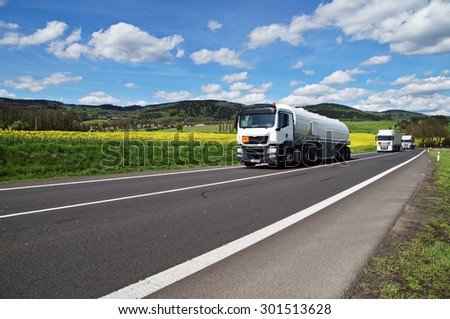White tanker and trucks driving along the asphalt road around the yellow flowering rapeseed field in countryside. Wooded mountains in the background. Blue sky with white clouds. #301513628