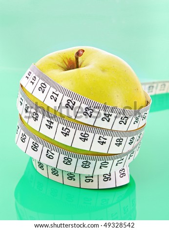 White tape measure around a green apple representing dieting