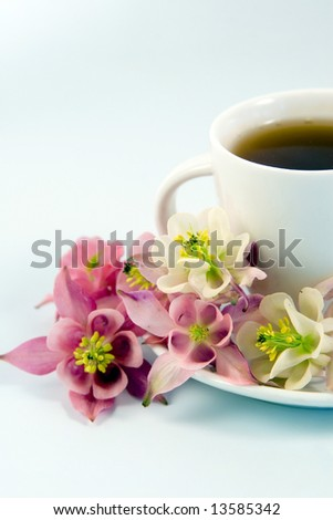 White teacup with tea and flowers
