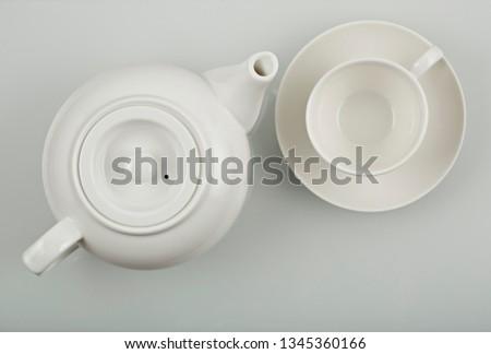 White teapot and white cap on the white background