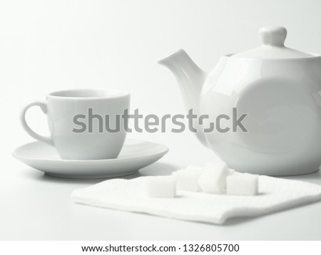 White teapot, white sugar and white cup on a white background