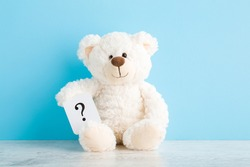 White teddy bear holding card of question sign on wooden table at light blue wall background. Pastel color. Closeup. Front view. Children issues.