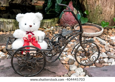 white teddy bear holding present on bicycle in garden background, love concept for valentines day