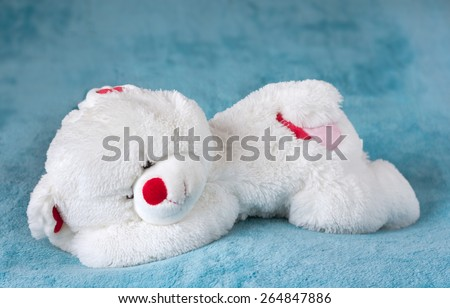 White teddy bear stuffed toy sleeping on a soft blue velvet blanket